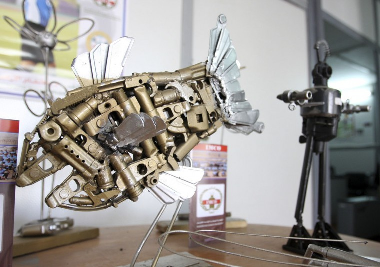 January 12, 2009: Metal sculptures of a fish and a robot, both made from pieces of destroyed weapons, are shown at the Iraqi Mine/Unexploded Ordnance (UXO) Clearance Organisation gallery in Baghdad. A dragonfly fashioned from a machine gun barrel, a rifle butt carved into the portrait an ancient Egyptian queen and a spent mortar round ashtray are just a few of the works Iraqi artists are making from weapons of war. Each day, the Iraqi Mines and Unexploded Ordnance Clearance Organisation (IMCO) destroys some 800 weapons, including AK-47 rifles, old school British Bren guns, mortar rounds and belt-fed machine guns collected by the U.S. forces during raids. (May Naji/Reuters)