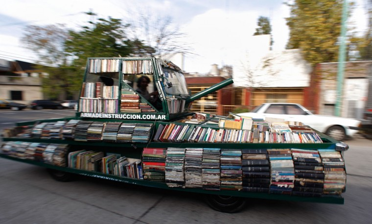"""June 8, 2009: Artist Raul Lemesoff drives his vehicle called """"Arma de Instruccion Masiva"""" (weapon of mass instruction) through the streets of Buenos Aires. The """"weapon of mass instruction"""" is a motorized sculpture made with books and is used by Lemesoff to distribute books as well as accept donations in order to supply schools in need, bars, country houses and any other venue where books might be lacking or rarely found. (Marcos Brindicci/Reuters)"""