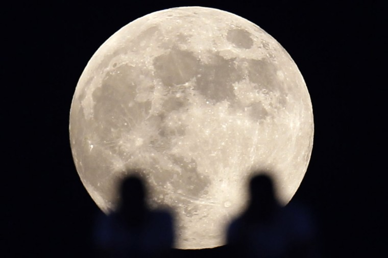 Fans watch the Egyptian Super Cup soccer match between Al-Ahly and Haras El Hodood during a full moon at Cairo Stadium July 25, 2010. (Amr Abdallah Dalsh/Reuters)