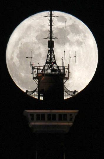 "The moon is seen behind the top of the radio and television tower 'Funkturm' in Berlin March 19, 2011. Saturday will see the rise of a full moon called a ""supermoon"" when it arrives at its closest point to the Earth in 2011, a distance of 221,565 miles or 356,575 km away. (Fabrizio Bensch/Baltimore Sun)"