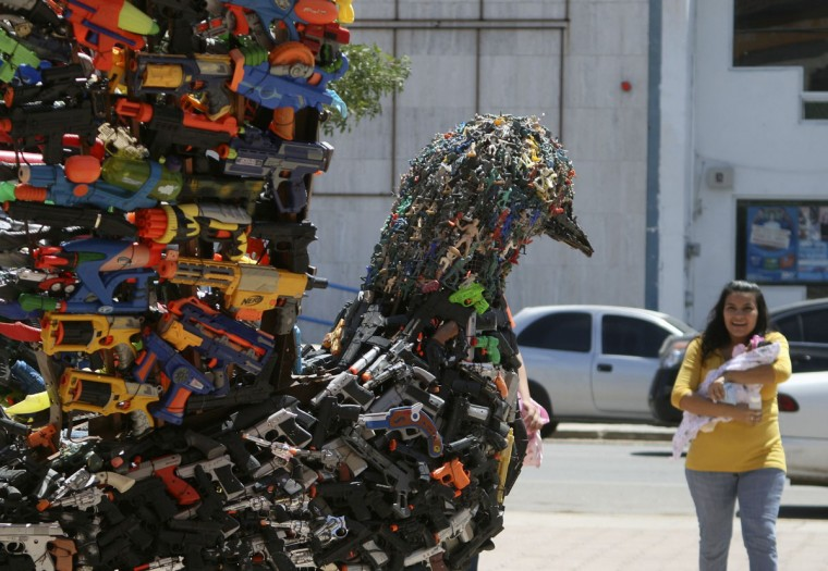 """April 7, 2011: A woman holding a baby looks at a sculpture of a dove made out of 8715 toy guns and toy soldiers in Caborca, Mexico. The sculpture was made by Antonio Estrada and elementary school students as part of the """"Jueguemos para Vivir (Let's play to live)"""" campaign for peace and a respectful environment for children. (Alonso Castillo/Reuters)"""