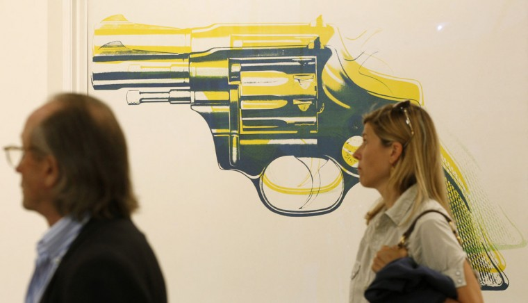 June 16, 2011: People walk past the painting 'Gun' from 1981 by late U.S. artist Andy Warhol (1928-1987) the Art Unlimited of the Art Basel art fair in Basel, Switzerland. (Arnd Wiegmann/Reuters)