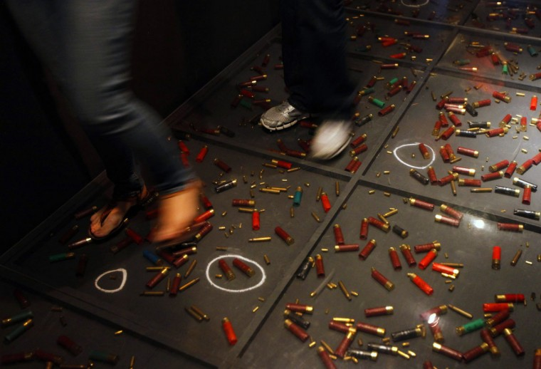 April 8, 2012: People walk over a floor displaying empty bullet shells at an art exhibition in Mexico City. The theme of the exhibition discusses the illegal arms trade between U.S. and Mexico. Authorities in Mexico have complained about the flood of weapons coming into their country from the United States, which they say facilitates the deadly war among drug cartels, causing more than 50,000 drug-related killings over the past five years. (Claudia Daut/Reuters)