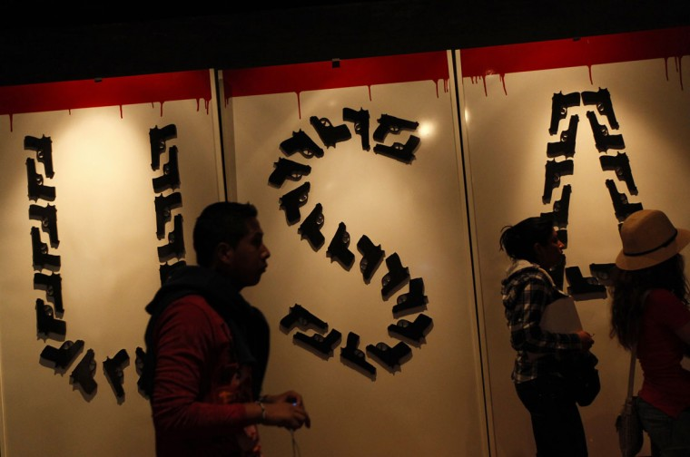 April 8, 2012: People walk past fake guns arranged to the letters that read USA at an art exhibition in Mexico City. The theme of the exhibition discusses the illegal arms trade between U.S. and Mexico. Authorities in Mexico have complained about the flood of weapons coming into their country from the United States, which they say facilitates the deadly war among drug cartels, causing more than 50,000 drug-related killings over the past five years. (Claudia Daut/Reuters)
