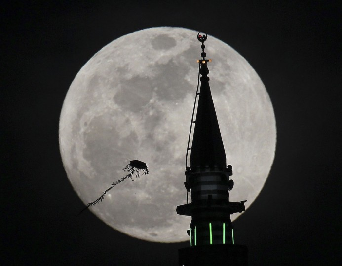 "The full moon rises behind a mosque as a kite flies in Amman May 5, 2012. Saturday will see the rise of a full moon called the ""supermoon"" when it arrives at its closest point to the Earth in 2012. (Ali Jarekji/Reuters)"