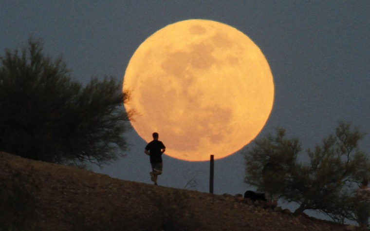 "A runner makes his way along a trail on a butte in front of the ""supermoon"" at Papago Park in Phoenix, Arizona May 5, 2012. (Darryl Webb/Reuters)"