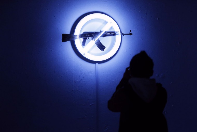 """September 26, 2012: A visitor looks at Langlands & Bell's """"Sign of the Times,"""" at the AKA Peace exhibition at the Institute for Contemporary Art (ICA) in central London. Bran Symondson, a former soldier, conceived the AKA Peace project, in which artists turn decommissioned AK47 assault rifles into works of art. (Andrew Winning/Reuters)"""