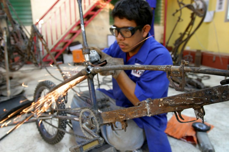 February 16, 2004: Cambodian artist Touun Tourneakea, 26, works on a bicycle sculpture made almost entirely of old AK-47 and M-16 rifles at a workshop in the capital Phnom Penh. The European Union is funding a project aimed at turning weapons into art in an effort to help Cambodia become a 'weapons-free society' after decades of war. (Chor Sokunthea/Reuters)