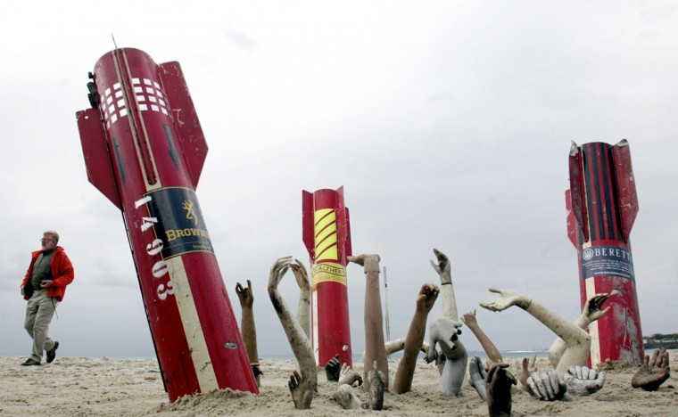 "September 14, 2003: A man walks near replica of missiles before a march for ""Brazil Without Weapons"" at Copacabana beach in Rio de Janeiro. Brazil is one of the most violent countries in Latin America, with a murder rate of 25 per 100,000 inhabitants. (Sergio Moraes/Reuters)"