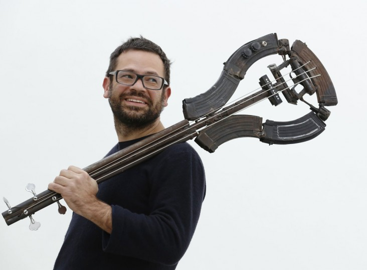 March 28, 2013: Mexican artist Pedro Reyes poses with one of his artworks, a bass guitar made out of recycled guns, at the Lisson Gallery in London. (Luke MacGregor/Reuters)