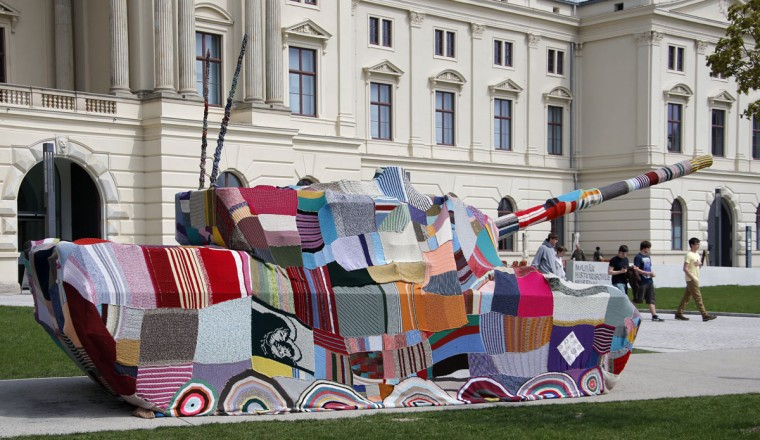"""April 25, 2013: People walk next to a German Leopard 1 tank in front of the Museum of Military History in Dresden, Germany. The tank is covered with knitting made by Dresden citizens, called """"Attack! Knitting for peace. Taking a stand against war and violence with a cross-generational handicrafts project."""" (Fabrizio Bensch/Reuters)"""