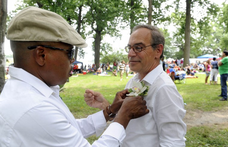 Tyrone Davis, left, pins a boutonniere on his soon-to-be spouse Don Bromer, right, before their wedding. Both are from Baltimore. (Barbara Haddock Taylor/Baltimore Sun)