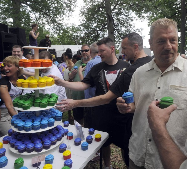 Just-married same-sex couples reach for rainbow cupcakes baked by Oooh So Sweet Bakery after their ceremony, which was conducted by Baltimore Mayor Stephanie Rawlings-Blake in Druid Hill Park during the Baltimore Pride Festival. (Barbara Haddock Taylor/Baltimore Sun)