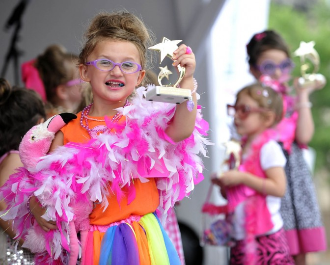 With gum in cheek and flamingo in tow, Madison Gauger, 3, Glen Burnie, holds up her trophy. She is competing in the Li'l Miss Hon competition. All contestants tied so they all received trophies. Honfest 2011. (Kim Hairston /Baltimore Sun)