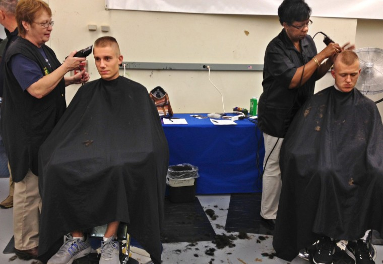 Two of the plebes get their haircut during induction day. (Erin Kirkland/Baltimore Sun)