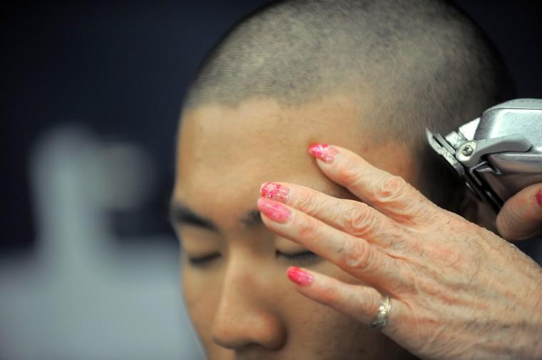 Lily Driver of Columbia trims the hair of Midshipman Alan Lee of South Carolina. (Erin Kirkland/Baltimore Sun)