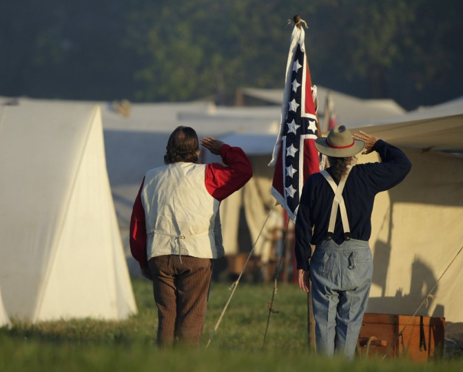 Soldiers salute their colors as the Confederate camp awakens at dawn during re-enactment activities recognizing the 150th anniversary of the U.S. Civil War battle in Gettysburg, Pennsylvania July 6, 2013. Gettysburg officials are expecting 250,000 visitors to visit the small south-central Pennsylvania borough of about 7,700 residents for the anniversary. REUTERS/Gary Cameron