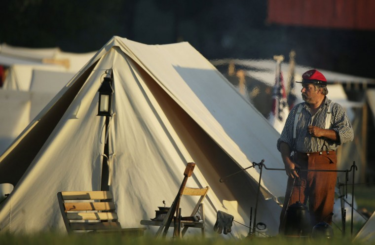 A soldier stands by his morning fire as the Confederate camp awakens at dawn during re-enactment activities recognizing the 150th anniversary of the U.S. Civil War battle in Gettysburg, Pennsylvania July 6, 2013. Gettysburg officials are expecting 250,000 visitors to visit the small south-central Pennsylvania borough of about 7,700 residents for the anniversary. REUTERS/Gary Cameron