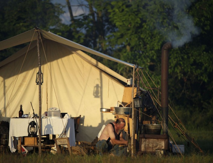A soldier tends his morning camp stove fire as the Confederate camp awakens at dawn during re-enactment activities recognizing the 150th anniversary of the U.S. Civil War battle in Gettysburg, Pennsylvania July 6, 2013. Gettysburg officials are expecting 250,000 visitors to visit the small south-central Pennsylvania borough of about 7,700 residents for the anniversary.
