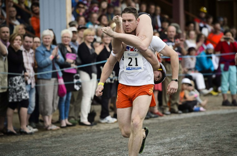 Matt Witko (L) and Hattie Archer (R) from England compete to take bronze during the Wife Carrying World Championships in Sonkajarvi, Finland on July 6, 2013. (Roni Rekomaa/ AFP Photo)