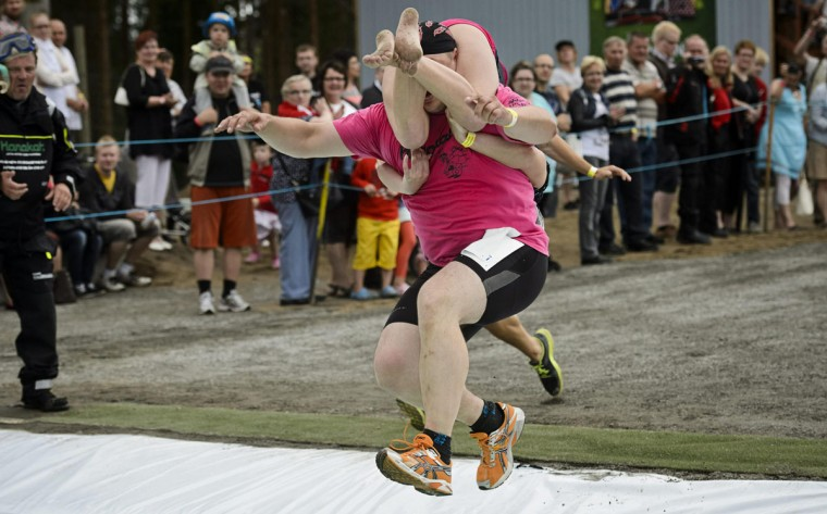 Joni Juntunen and Jaana Haavikko from Finland compete to take fifth place during the Wife Carrying World Championship competition in Sonkajarvi July 6, 2013. (Roni Rekomaa/ AFP Photo)
