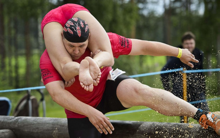 Joni Juntunen and Jaana Haavikko from Finland compete to take fifth place during the Wife Carrying World Championships in Sonkajarvi, Finland on July 6, 2013. (Roni Rekomaa/ AFP Photo)