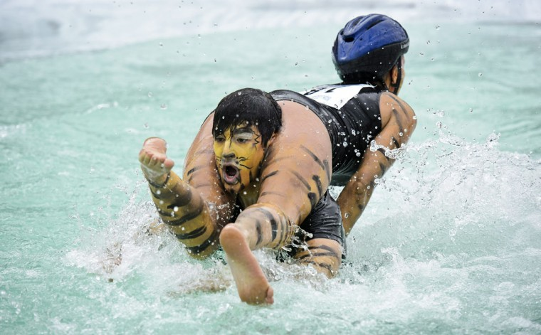 Aleksander Pihlainen and Siiri Salli from Finland compete during the Wife Carrying World Championships in Sonkajarvi, Finland on July 6, 2013. (Roni Rekomaa/ AFP Photo)