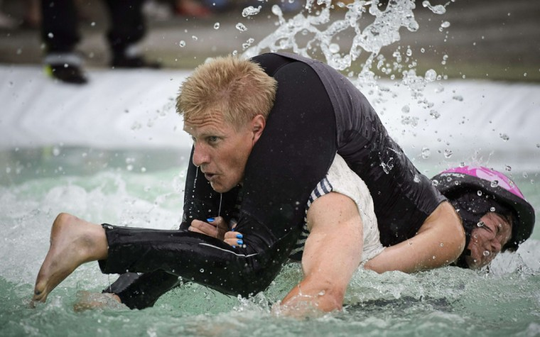 Taisto Miettinen and Kristiina Haapanen from Finland compete during the Wife Carrying World Championships in Sonkajarvi, Finland on July 6, 2013. (Roni Rekomaa/ AFP Photo)