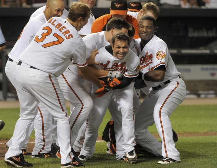 Brian Roberts gets mobbed by his teammates, including relief pitcher Matt Albers (37), after his 10th inning lead-off homer won an August 2010 game for the Orioles, 3-2. (Gene Sweeney Jr/Baltimore Sun)