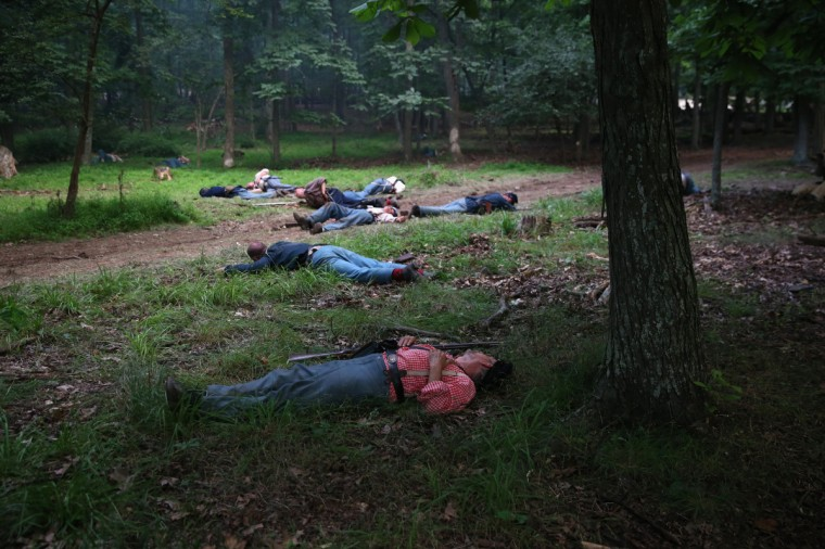 """Civil War Union re-enactors lie where they were """"shot"""" during a three-day Battle of Gettysburg re-enactment on June 29, 2013 in Gettysburg, Pennsylvania. (John Moore/Getty Images)"""