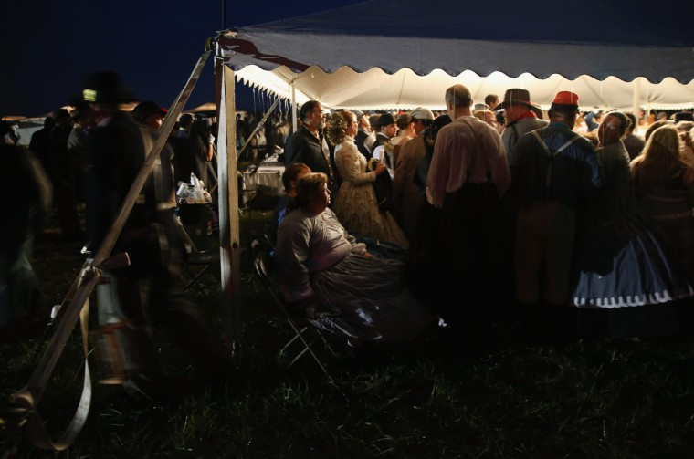 American Civil War re-enactors take shelter from a downpoar during an evening ball as part of a three-day Battle of Gettysburg re-enactment on June 29, 2013 in Gettysburg, Pennsylvania. (John Moore/Getty Images)
