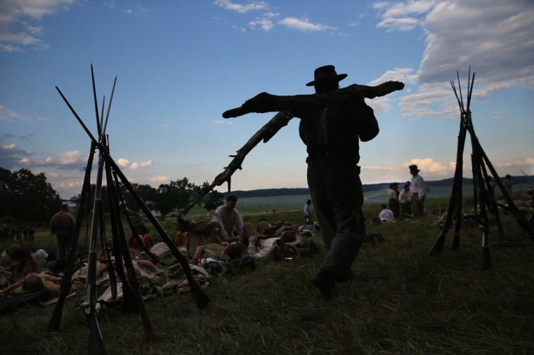 Confederate Civil War re-enactors gather wood to cook at sunset as part of a three-day Battle of Gettysburg re-enactment on June 29, 2013 in Gettysburg, Pennsylvania. (John Moore/Getty Images)