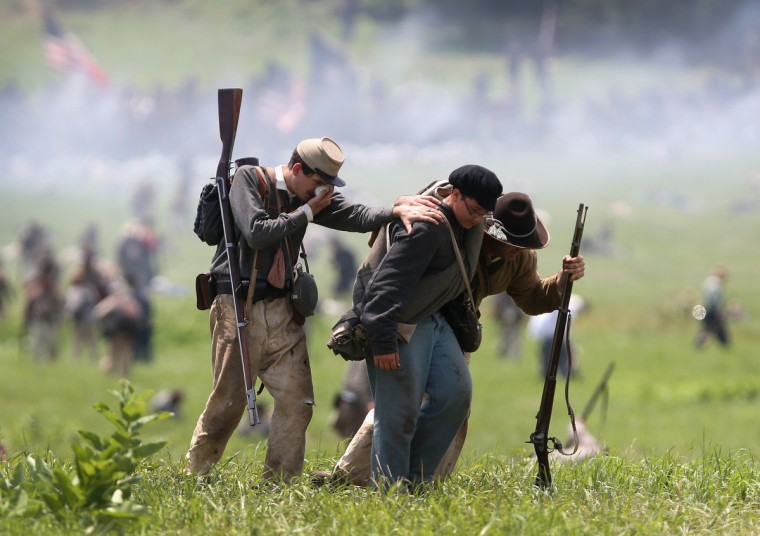 Confederate Civil War re-enactors flee the battlefield following Pickett's Charge on the last day of a Battle of Gettysburg re-enactment on June 30, 2013 in Gettysburg, Pennsylvania. (John Moore/Getty Images)