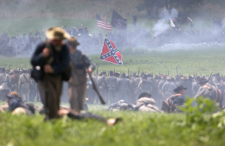 Confederate Civil War re-enactors push past wounded commrades towards the Union line while performing Pickett's Charge on the last day of a Battle of Gettysburg re-enactment on June 30, 2013 in Gettysburg, Pennsylvania. (John Moore/Getty Images)