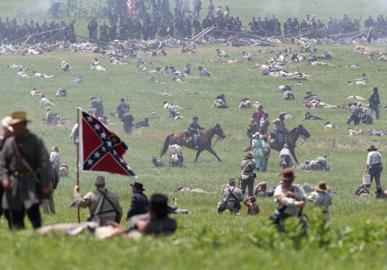 """Wounded"" Civil War re-enactors litter the battlefield at the end of Pickett's Charge on the last day of a Battle of Gettysburg re-enactment on June 30, 2013 in Gettysburg, Pennsylvania. (John Moore/Getty Images)"