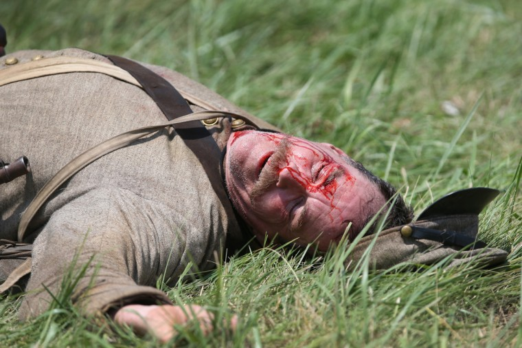 """A Confederate Civil War re-enactor """"expires"""" on the battlefield at the end of Pickett's Charge on the last day of a Battle of Gettysburg re-enactment on June 30, 2013 in Gettysburg, Pennsylvania. (John Moore/Getty Images)"""