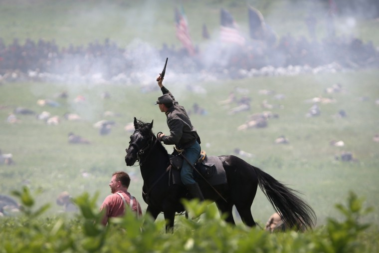 A Confederate Civil War re-enactor shoots at Union soldiers during Pickett's Charge on the last day of a Battle of Gettysburg re-enactment on June 30, 2013 in Gettysburg, Pennsylvania. (John Moore/Getty Images)