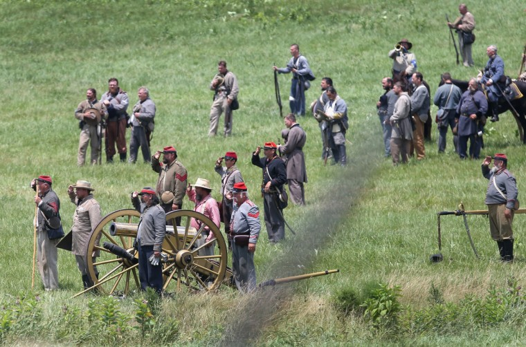 """Confederate Civil War re-enactors salute as a bugler plays """"Taps"""" following Pickett's Charge on the last day of a Battle of Gettysburg re-enactment on June 30, 2013 in Gettysburg, Pennsylvania. (John Moore/Getty Images)"""