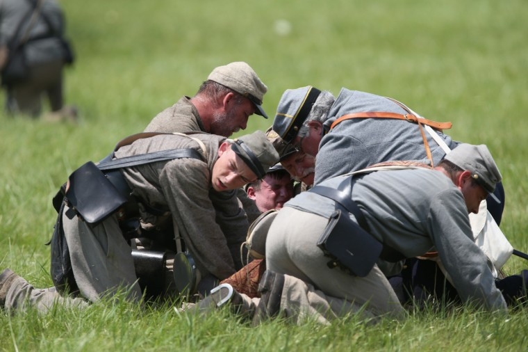 "Confederate Civil War re-enactors aid a ""wounded"" commrade during Pickett's Charge on the last day of a Battle of Gettysburg re-enactment on June 30, 2013 in Gettysburg, Pennsylvania. (John Moore/Getty Images)"