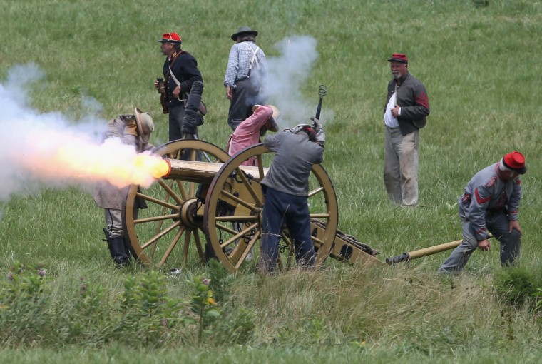 Confederate Civil War re-enactors fire a cannon towards Union positions during Pickett's Charge on the last day of a Battle of Gettysburg re-enactment on June 30, 2013 in Gettysburg, Pennsylvania. (John Moore/Getty Images)