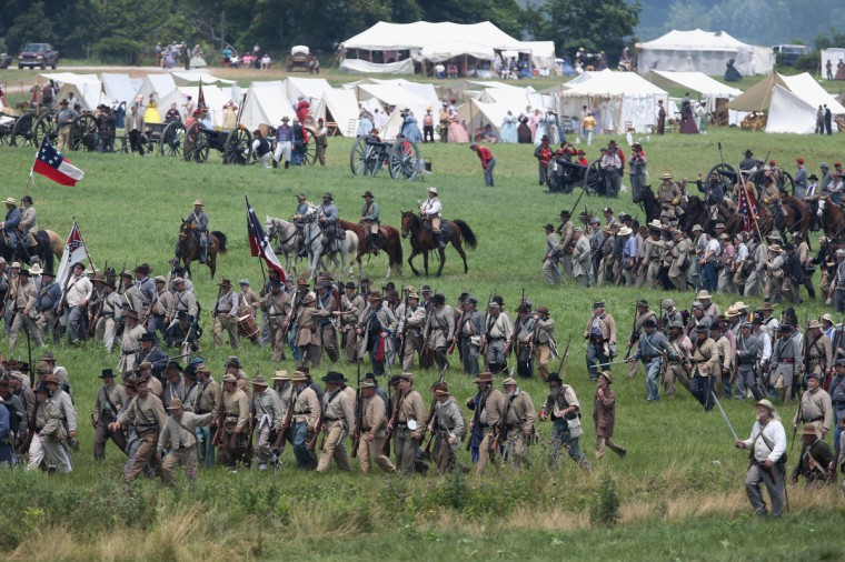 Confederate Civil War re-enactors march towards Union positions during Pickett's Charge on the last day of a Battle of Gettysburg re-enactment on June 30, 2013 in Gettysburg, Pennsylvania. Some 8,000 re-enactors from the Blue Gray Alliance participated in the event, marking the 150th anniversary of the July 1-3, 1863 Battle of Gettysburg. Confederate General Robert E. Lee's Army of Northern Virginia was routed during the doomed frontal assault, considered the turning point in the Civil War and a watershed moment in U.S. history. Union and Confederate armies suffered a combined total of up to 51,000 casualties over three days, the highest number of any battle in the four-year war. Pickett's charge was named for the Confederate Maj. General George Pickett, whose division of rebel troops was decimated in the attack. (John Moore/Getty Images)