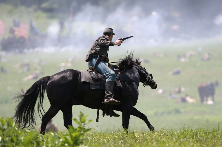 A Confederate Civil War cavalry re-enactor shoots at Union soldiers during Pickett's Charge on the last day of a Battle of Gettysburg re-enactment on June 30, 2013 in Gettysburg, Pennsylvania. (John Moore/Getty Images)