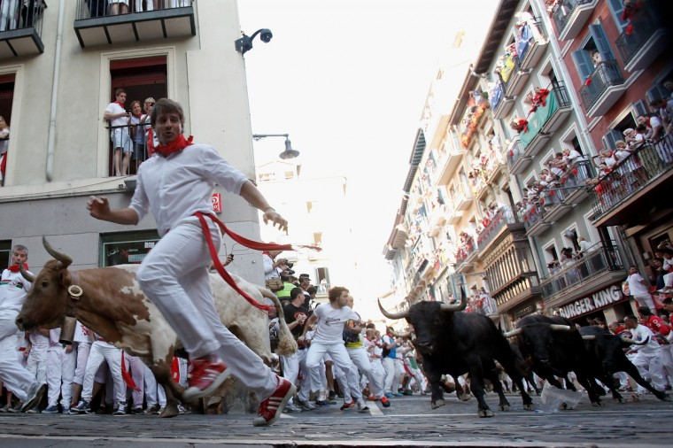 Revellers run with Dolores Aguirre's ranch fighting bulls at Curva Estafeta during the third day of the San Fermin Running Of The Bulls festival in Pamplona, Spain. (Pablo Blazquez Dominguez/Getty Images)