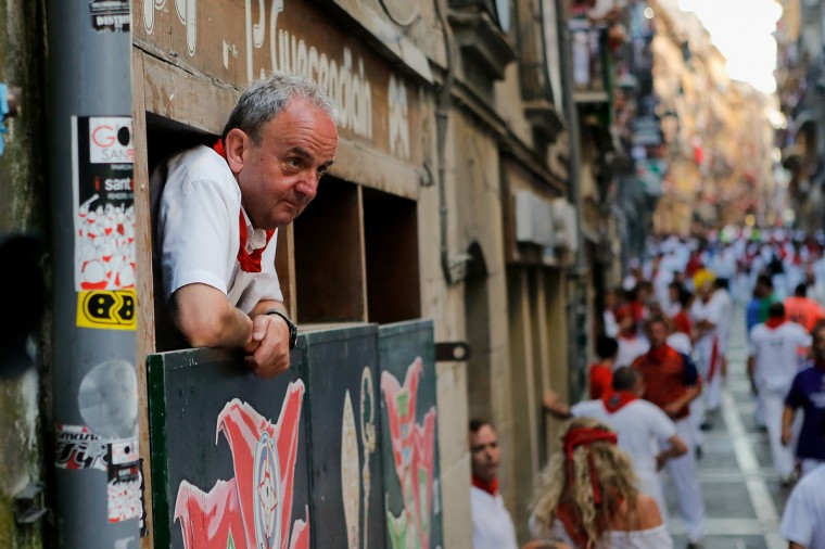 A man watches the Dolores Aguirre's ranch fighting bulls running at Curva Estafeta during the third day of the San Fermin Running Of The Bulls festival, in Pamplona, Spain. (Pablo Blazquez Dominguez/Getty Images)