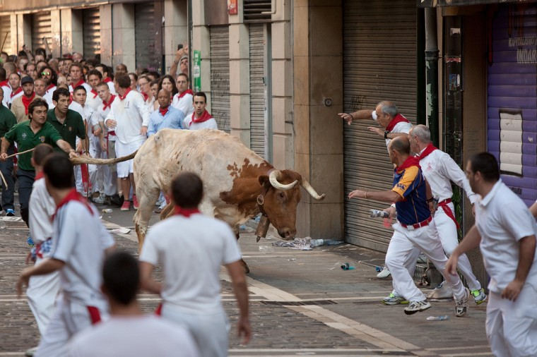 A steer runs towards revellers during the Dolores Aguirre's ranch fighting bulls running near Curva Estafeta on the third day of the San Fermin Running Of The Bulls festival in Pamplona, Spain.(Pablo Blazquez Dominguez/Getty Images)