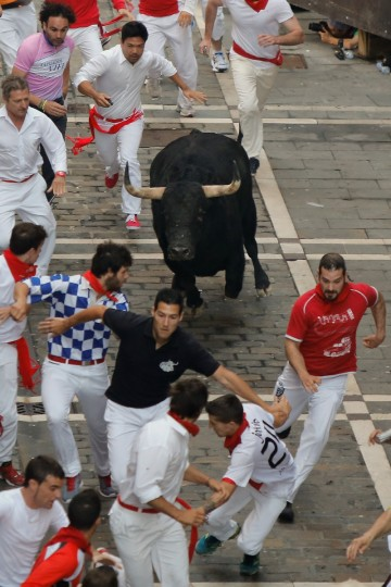 Revellers run with a Valdefresno's ranch fighting bull at Calle Estafeta during the fourth day of the San Fermin Running Of The Bulls festival, . (Pablo Blazquez Dominguez/Getty Images)