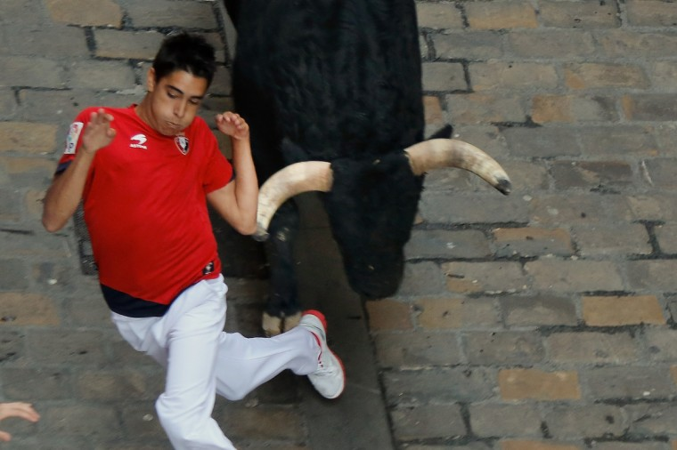 A reveller eludes a Valdefresno's ranch fighting bull's horn at Calle Estafeta during the fourth day of the San Fermin Running Of The Bulls festival. (Pablo Blazquez Dominguez/Getty Images)