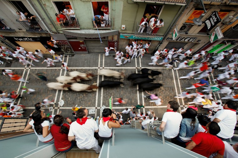 Revellers run with Valdefresno's ranch fighting bulls at Calle Estafeta during the fourth day of the San Fermin Running Of The Bulls festival. (Pablo Blazquez Dominguez/Getty Images)