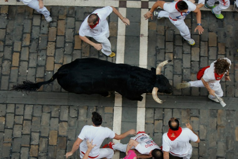 Revellers run with a Valdefresno's ranch fighting bull at Calle Estafeta during the fourth day of the San Fermin Running Of The Bulls festival, on July 9, 2013 in Pamplona, Spain. (Pablo Blazquez Dominguez/Getty Images)
