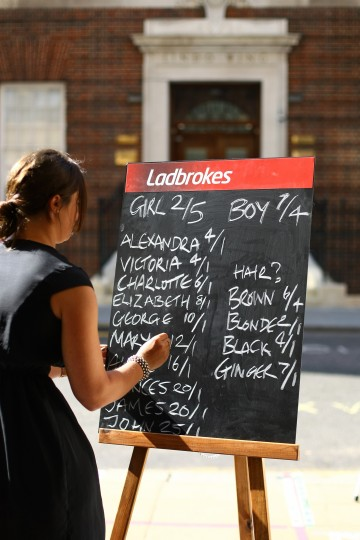 Public Relations Executive of Ladbrokes, Jessica Bridge, writes today's odds for the royal baby on a chalk board in front of the Lindo Wing as the UK prepares for the birth of the first child of The Duke and Duchess of Cambridge at St Mary's Hospital in London, England. (Jordan Mansfield/Getty Images)